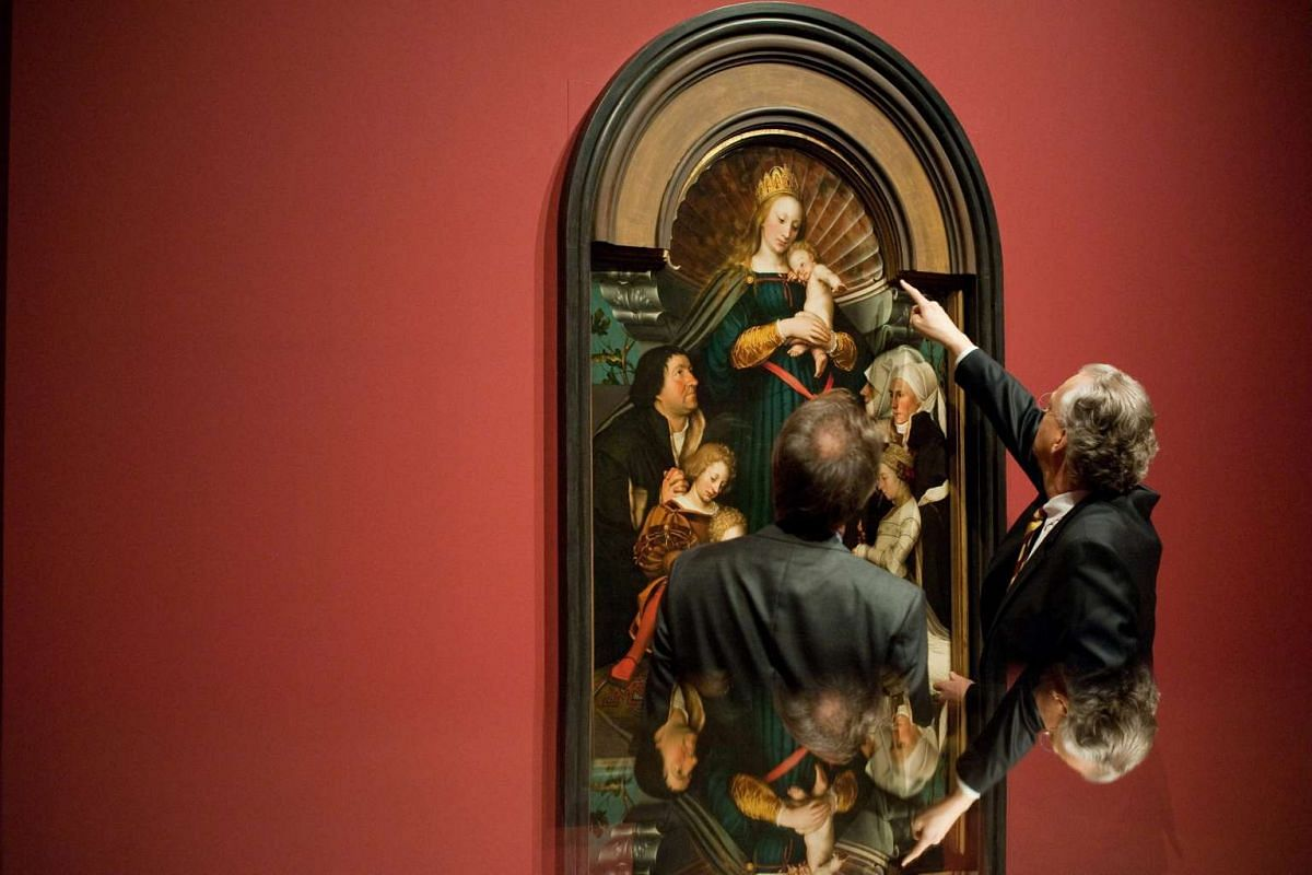 Curator Stephan Kemperdick (L) and Michael Eissenhauer (R), the director general of the National Museums in Berlin, look at the painting The Madonna Of Jakob Meyer zum Hasen by German artist Hans Holbein the Younger at the Bode-Museum in Berlin, Germ
