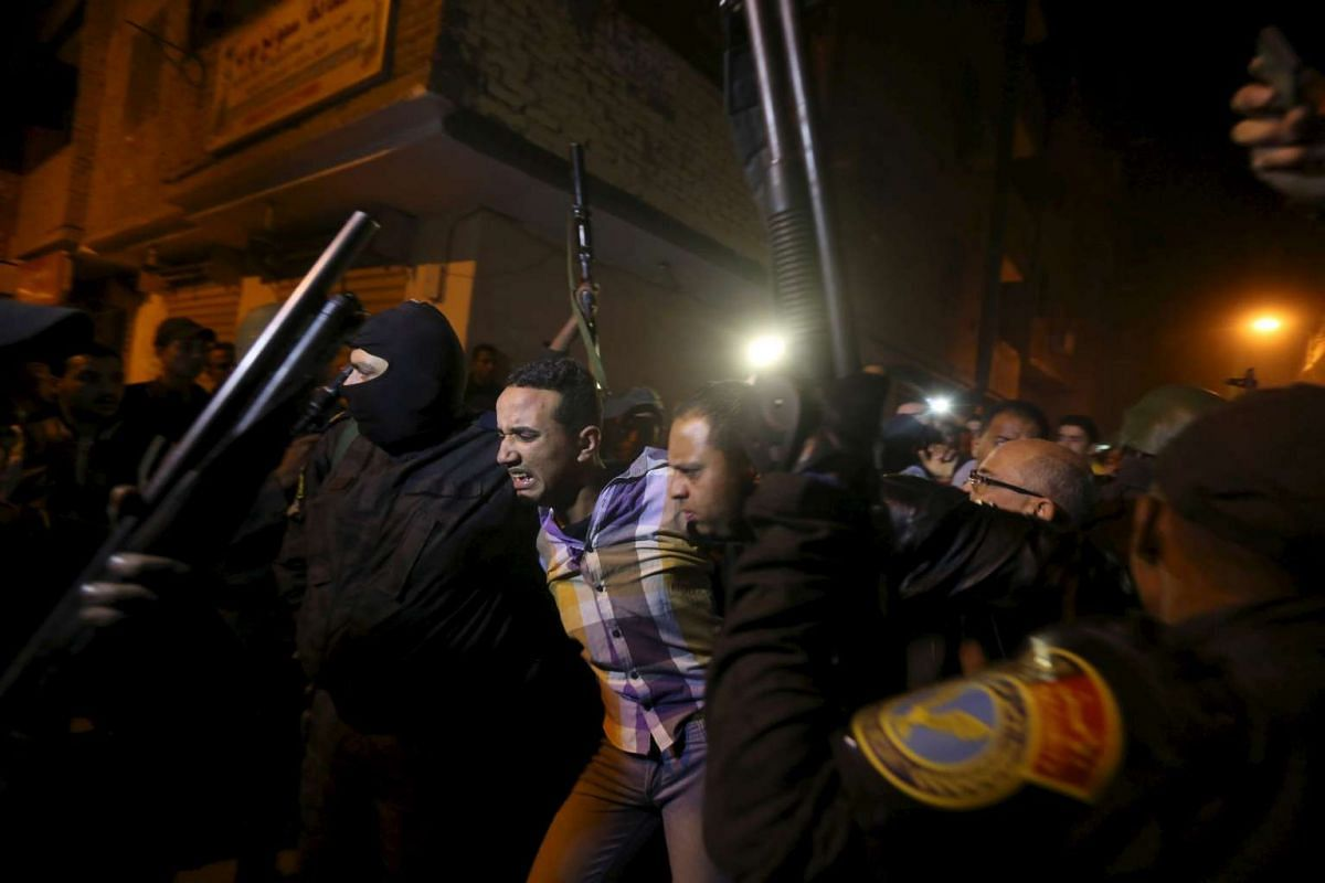 Security forces detain a man at the scene of a bomb blast in a main street in Giza, Egypt, Jan 21, 2016. PHOTO: REUTERS