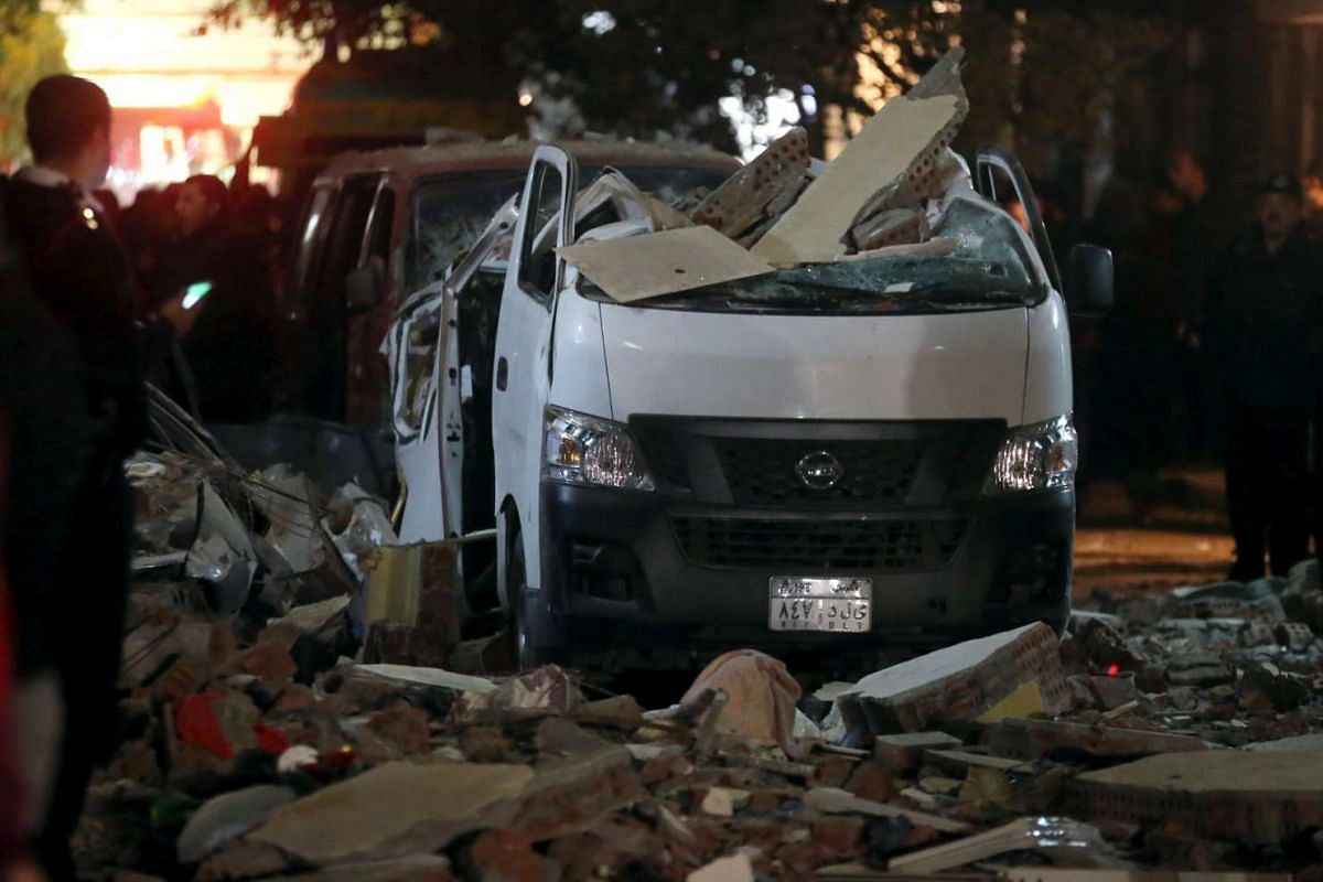 Damaged cars are seen at the scene of a bomb blast in Giza, Egypt, Jan 21, 2016. The bomb attack killed six people, including three policemen. PHOTO: REUTERS
