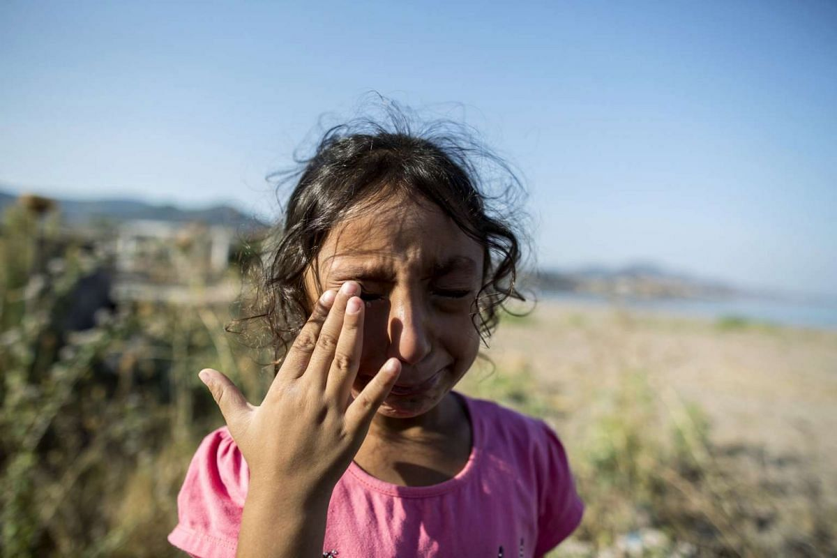 Yasmine, a six-year-old migrant from Deir Al Zour in war-torn Syria, cries at the beach after arriving on the Greek island of Lesbos on Sept 11, 2015.