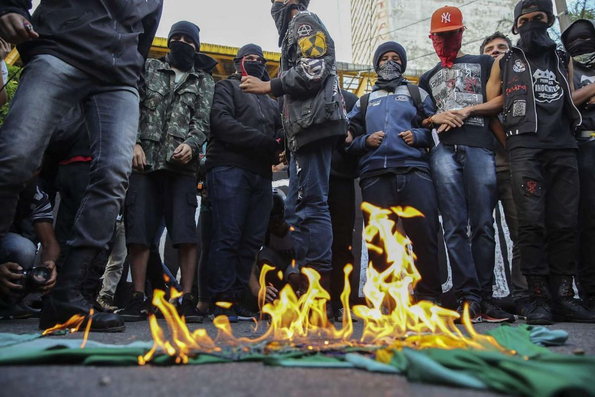 Demonstrators burn a Brazilian national flag during a protest against the hike in public transport prices in the city, in Sao Paulo, Brazil, Jan 21, 2016. PHOTO: EPA