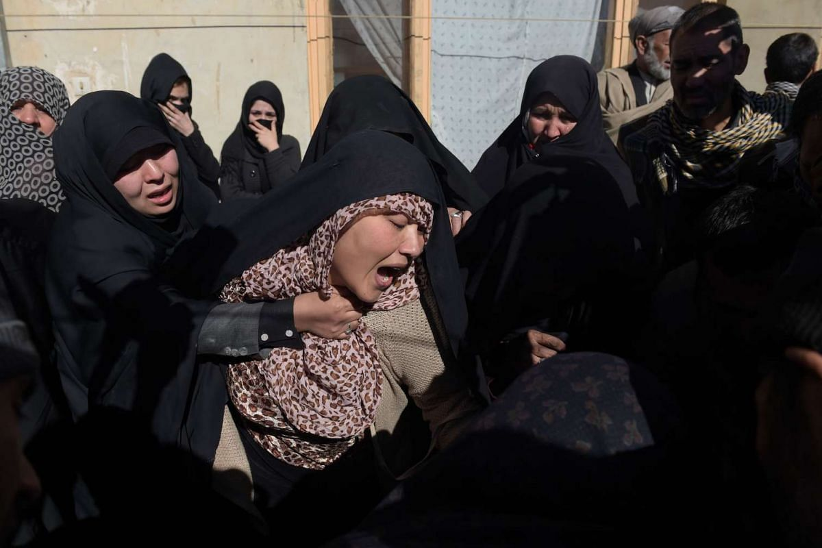 Afghan relatives react during the funeral for Saeed Jawad Hossini, 29, who was killed in a suicide attack on a minibus carrying employees of Afghan TV channel Tolo in Kabul on Jan 21, 2016. PHOTO: AFP