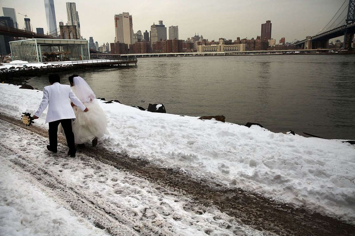A newly married couple walk in the snow on the first workday following a blizzard that set a new single-day record for snowfall in both New York and Washington DC on Jan 25, 2016, in New York City.