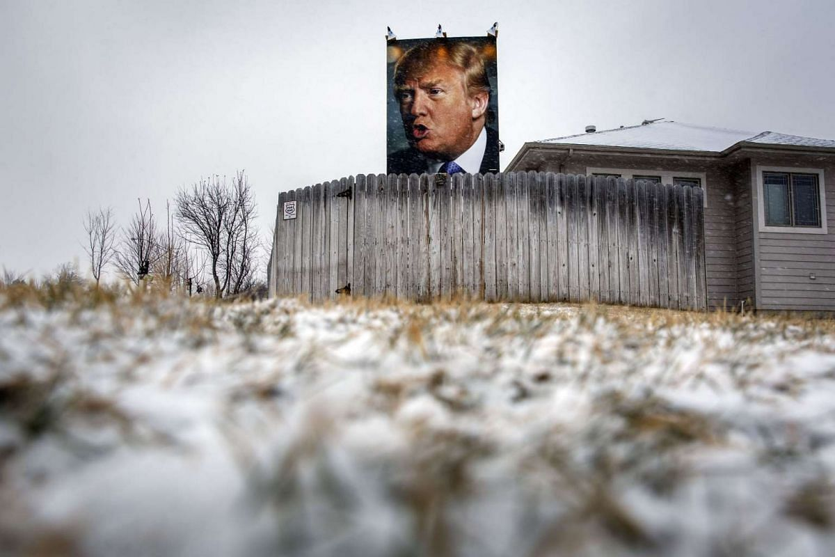 A poster of Donald Trump outside a home as snow falls in Iowa on Jan 25, 2016.