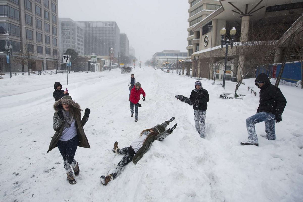A group of students visiting the Washington DC area from Louisiana play in the snow along Wisconsin Avenue during a major blizzard in Maryland on Jan 23, 2016.