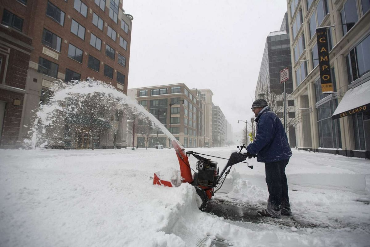 A man struggles to clear snow from a sidewalk during a major blizzard in Washington DC on Jan 23, 2016.