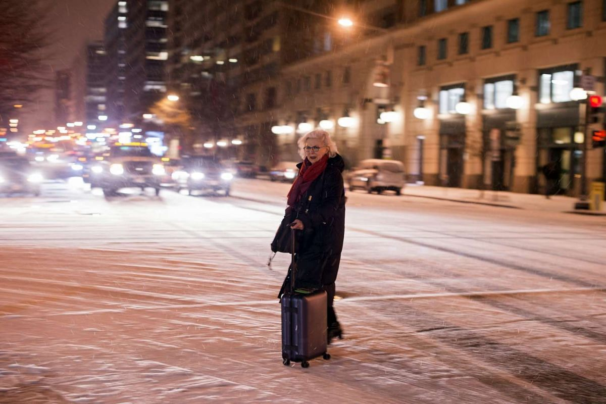 A pedestrian walks across a snow-covered road during snowfall, in downtown Washington, DC, on Jan 20, 2016. Meteorologists on Jan 19 warned that the season's first significant winter storm could be fast approaching.