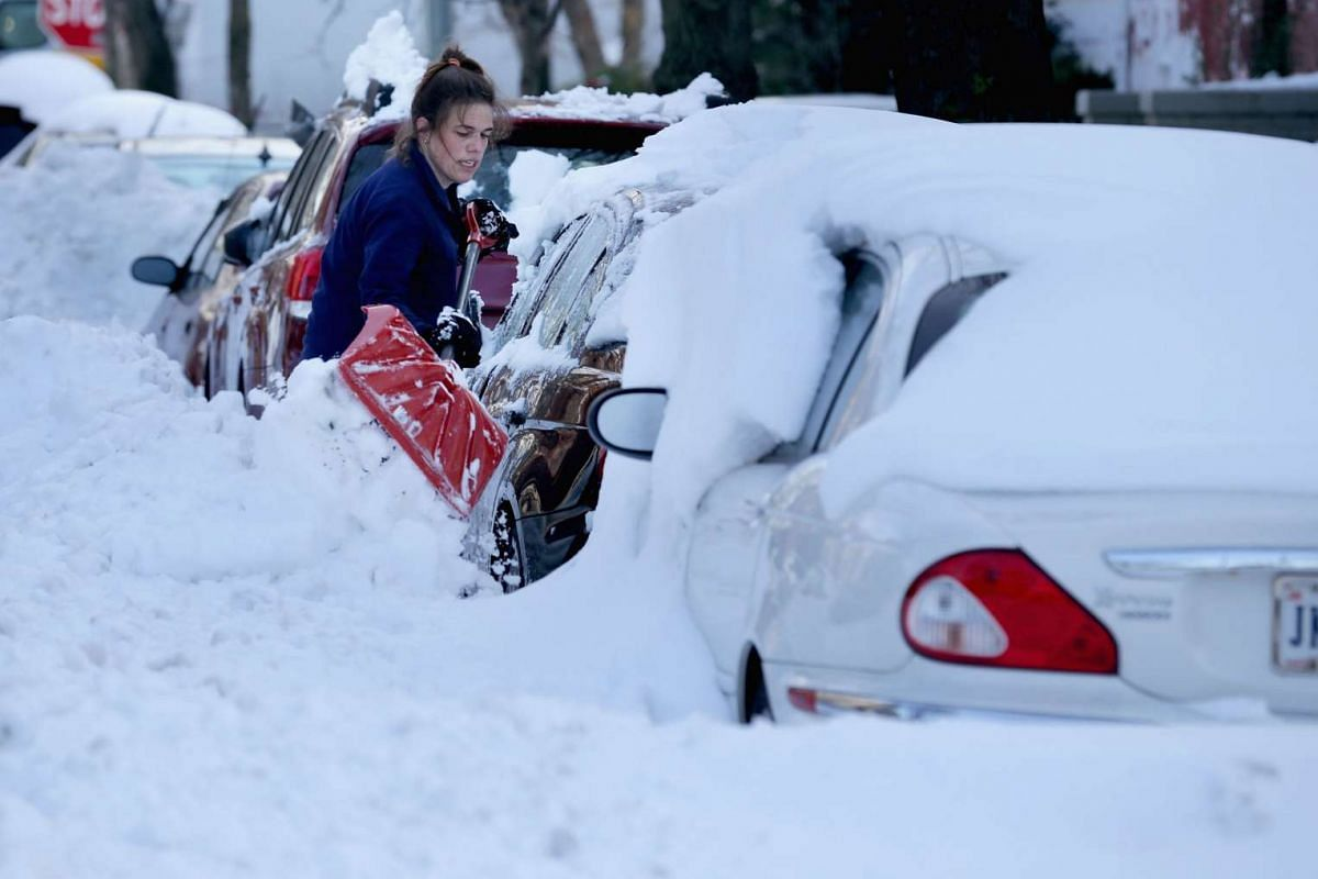 Residents of the Capitol Hill neighbourhood work to clean snow off their cars in Washington on Jan 25, 2016.