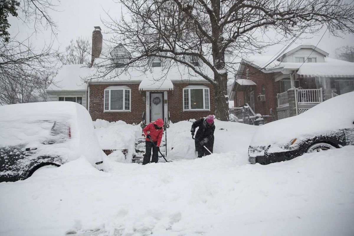 People shovel snow on the sidewalk in the Woodridge neighborhood in north-east Washington DC on Jan 23, 2016.