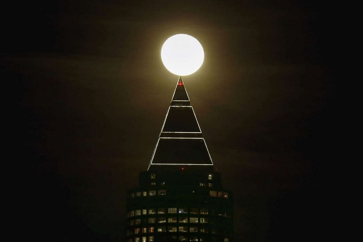 The moon is seen next to the Messeturm (fair tower) in Frankfurt, Germany, on Jan 25, 2016.