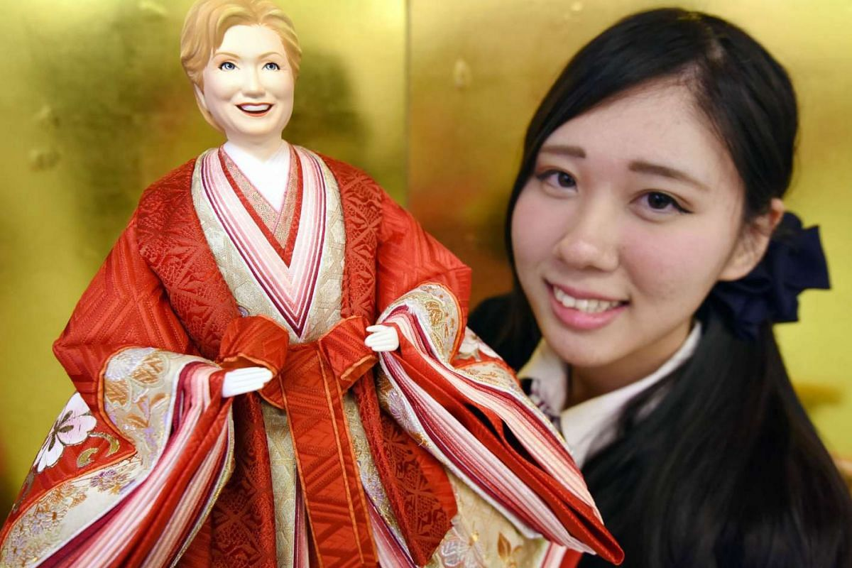 "An employee for Japanese dollmaker Kyugetsu unveiling a ""hina"" doll of US Democratic candidate Hillary Clinton at the company's showroom in Tokyo on Jan 27, ahead of the country's Hina Matsuri, or Girls' Day, on March 3."