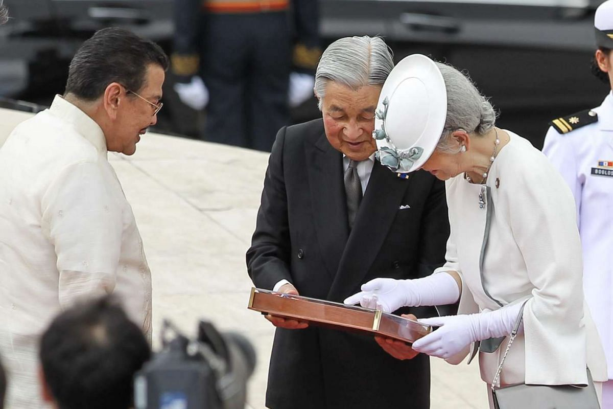 Former President and now Manila Mayor Joseph Estrada (left) presents Japan's Emperor Akihito (centre) and Empress Michiko with a gift during a wreath laying ceremony at the monument of Philippine national hero Jose Rizal at the Luneta Park in Manila,