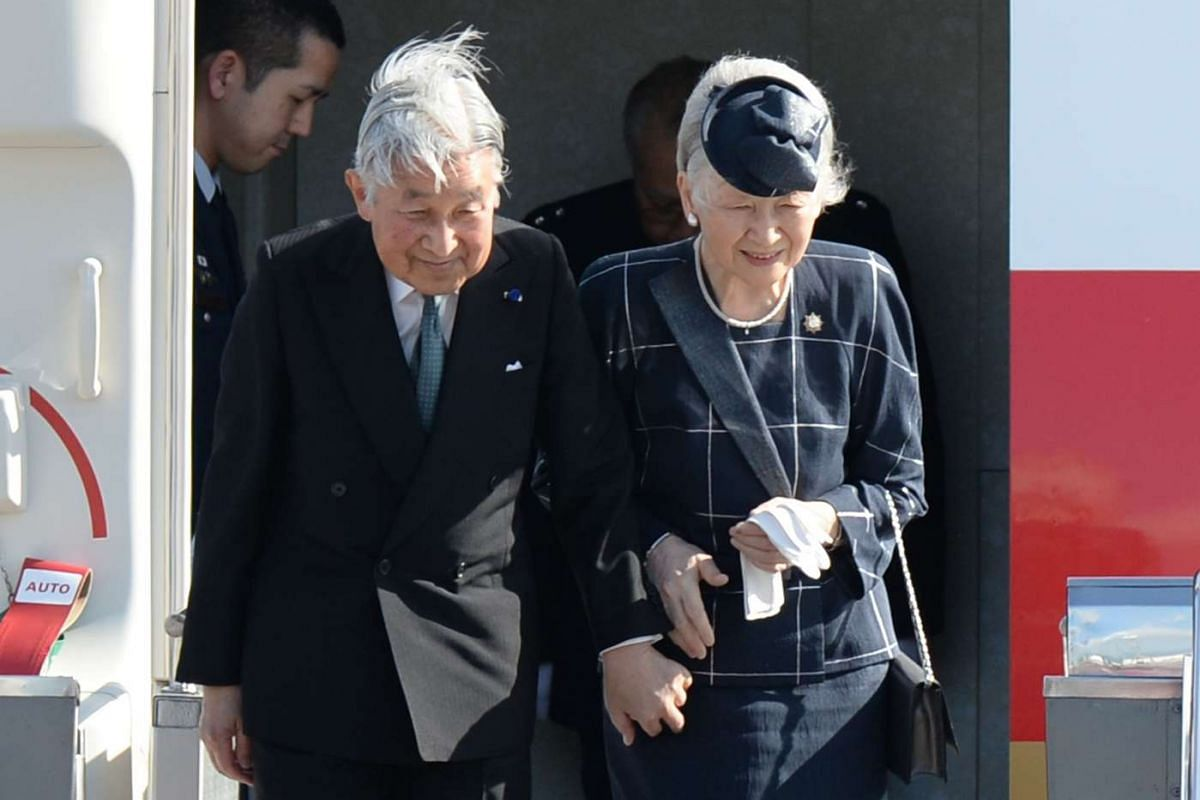 Emperor Akihito and his wife Empress Michiko acknowledge well wishers as they prepare to disembark from a plane shortly after arriving at the international airport in Manila on Jan 26.