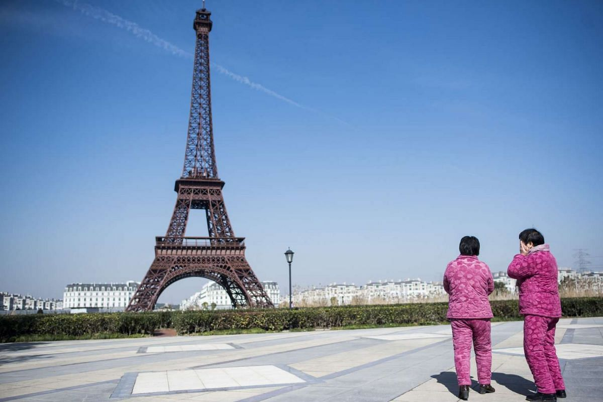 This Jan 26 picture shows two Chinese women in matching pyjamas standing near a replica of the Eiffel Tower in Tianducheng, a luxury real estate development in eastern China's Zhejiang province.