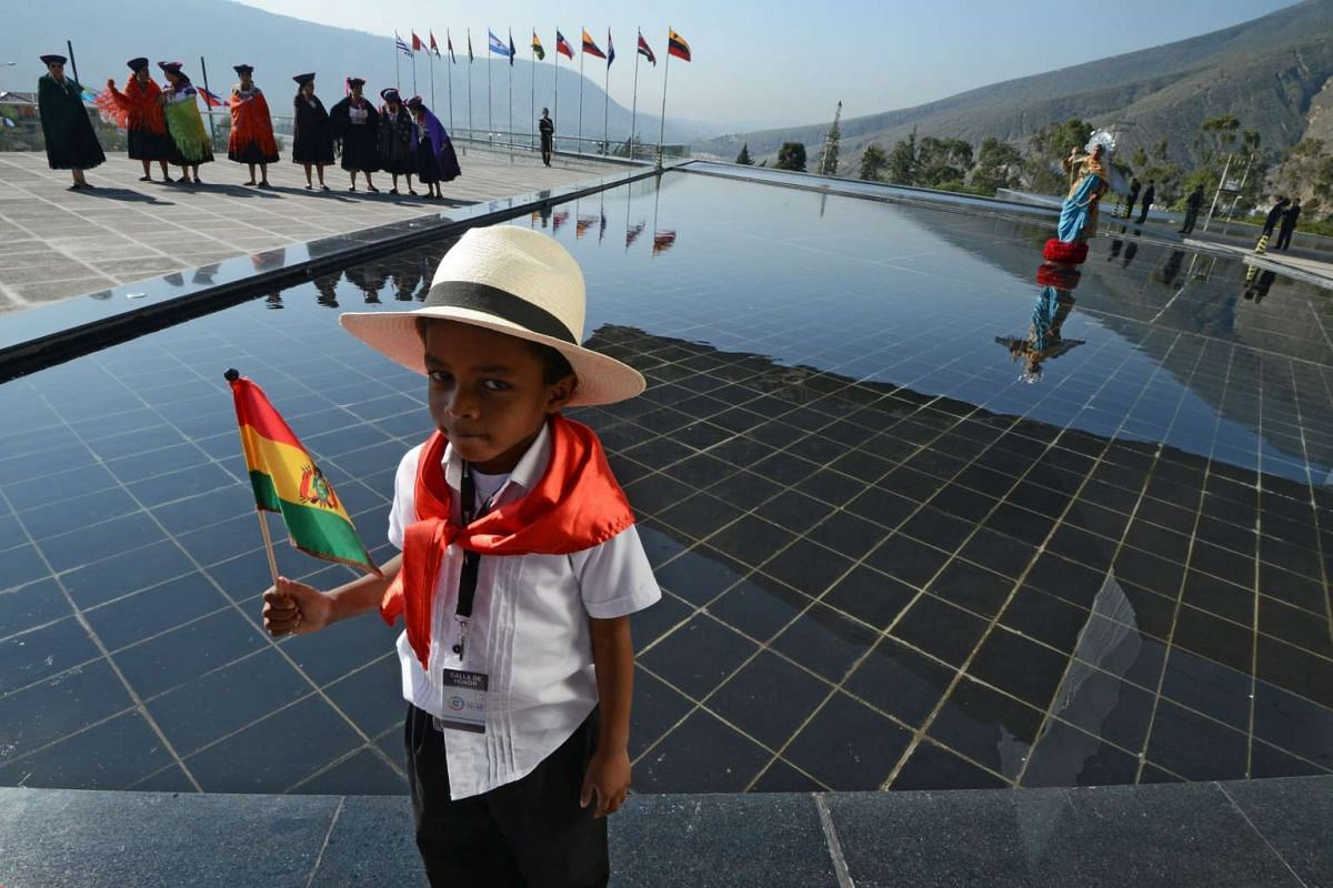 A child stands next to a pond of the United Nations South American Nations headquarters in Quito, where the IV Community of Latin American and Caribbean States summit is held on Jan 27, 2016.