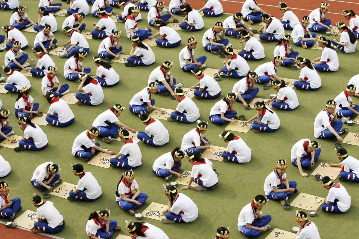 """Students play the board game """"Go"""", known as """"Weiqi"""" in Chinese at a primary school in Suzhou, Jiangsu province on April 30, 2008. Scientists said on Wednesday (Jan 27) that they created a computer program that beat a professional human player at the"""