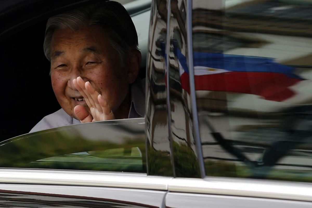 Japan Emperor Akihito waves from a vehicle as a motorcade passes in Manila, Philippines, on Jan 28, 2016.
