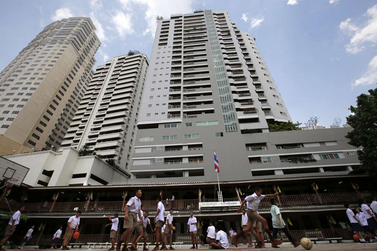 Schoolchildren playing at the Wannawit School, dwarfed by towering apartments and other high rise buildings in central Bangkok, Thailand.