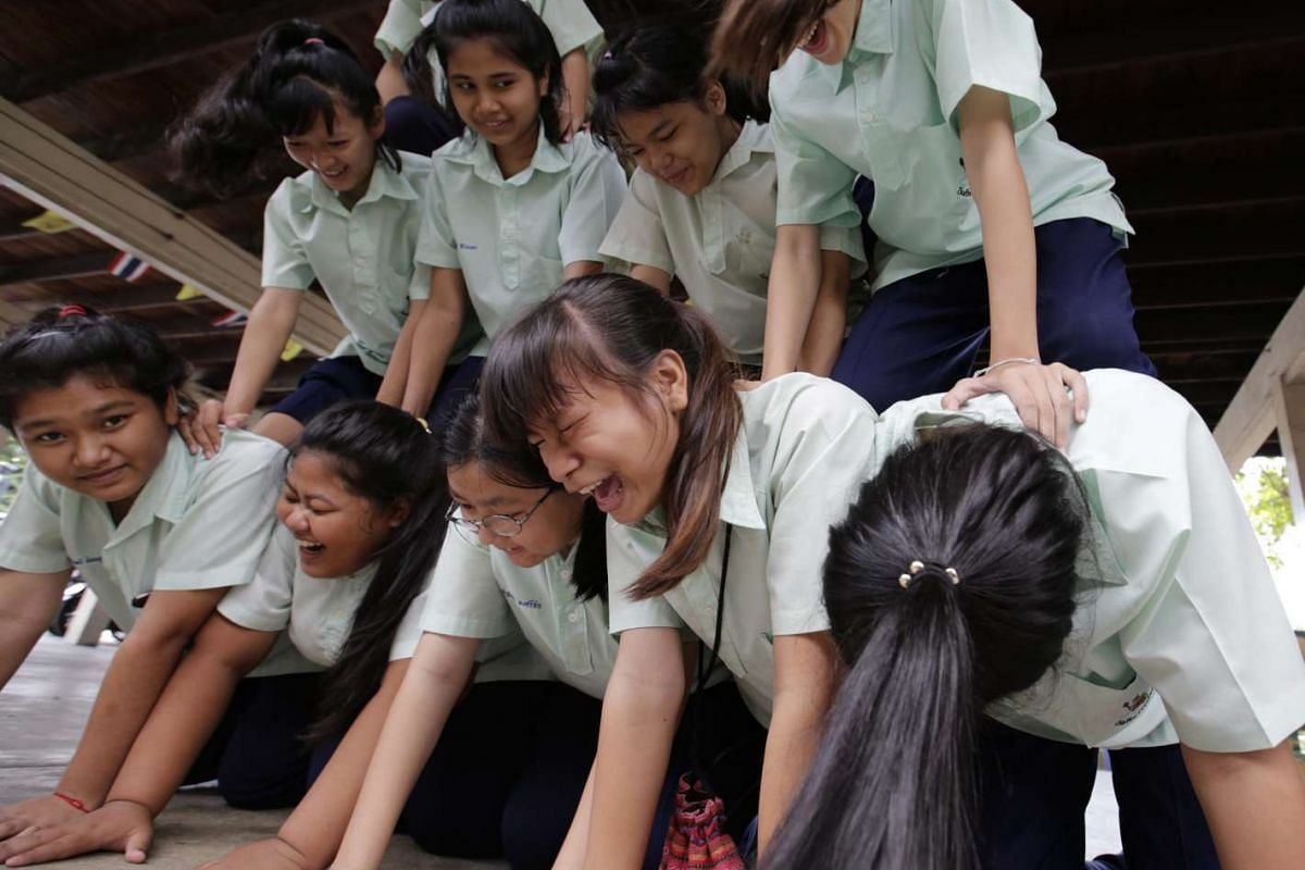 Thai students laughing as they build a human tower during their physical fitness class at the Wannawit School.