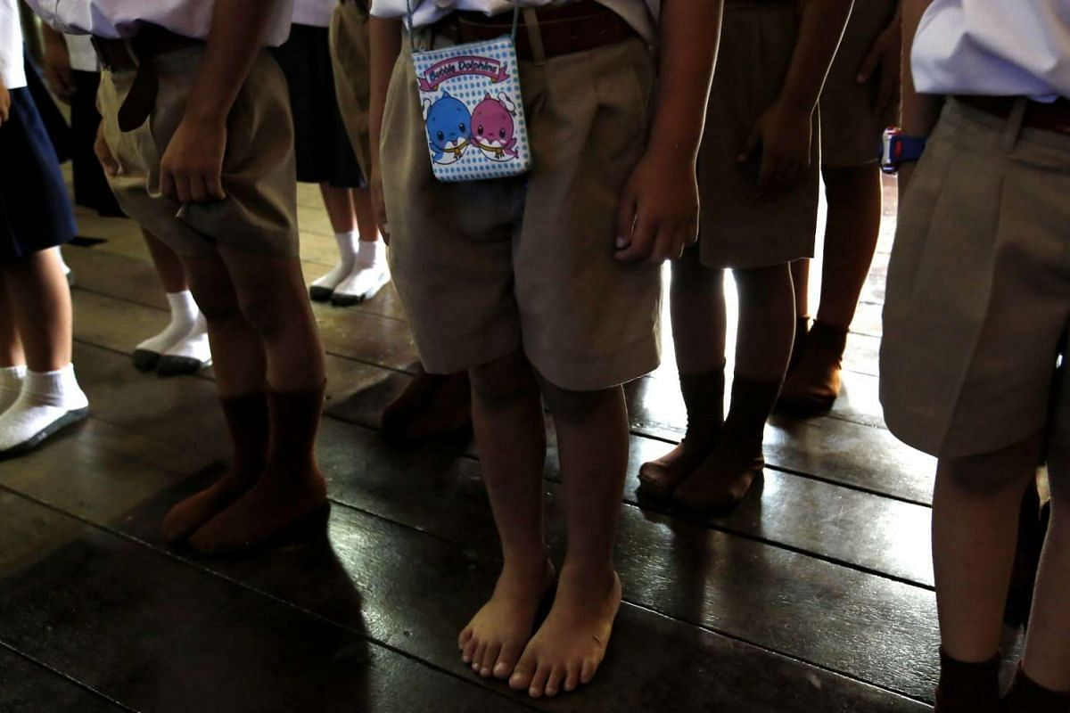 Schoolchildren standing at attention while singing the Thai national anthem in the Wannawit School.
