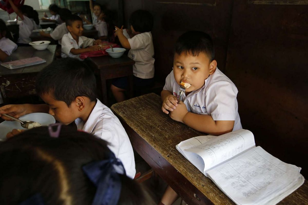 A Thai primary school student eating a sausage at the wooden Wannawit School.