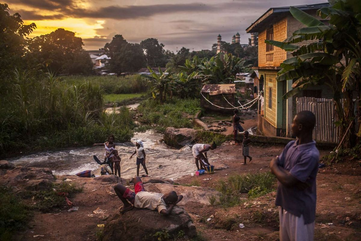 Pete Muller's winning sequence of photographs on Ebola includes one of residents of the town of Kailahun in eastern Sierra Leone, a place most heavily affected by the outbreak, along a river at dusk.