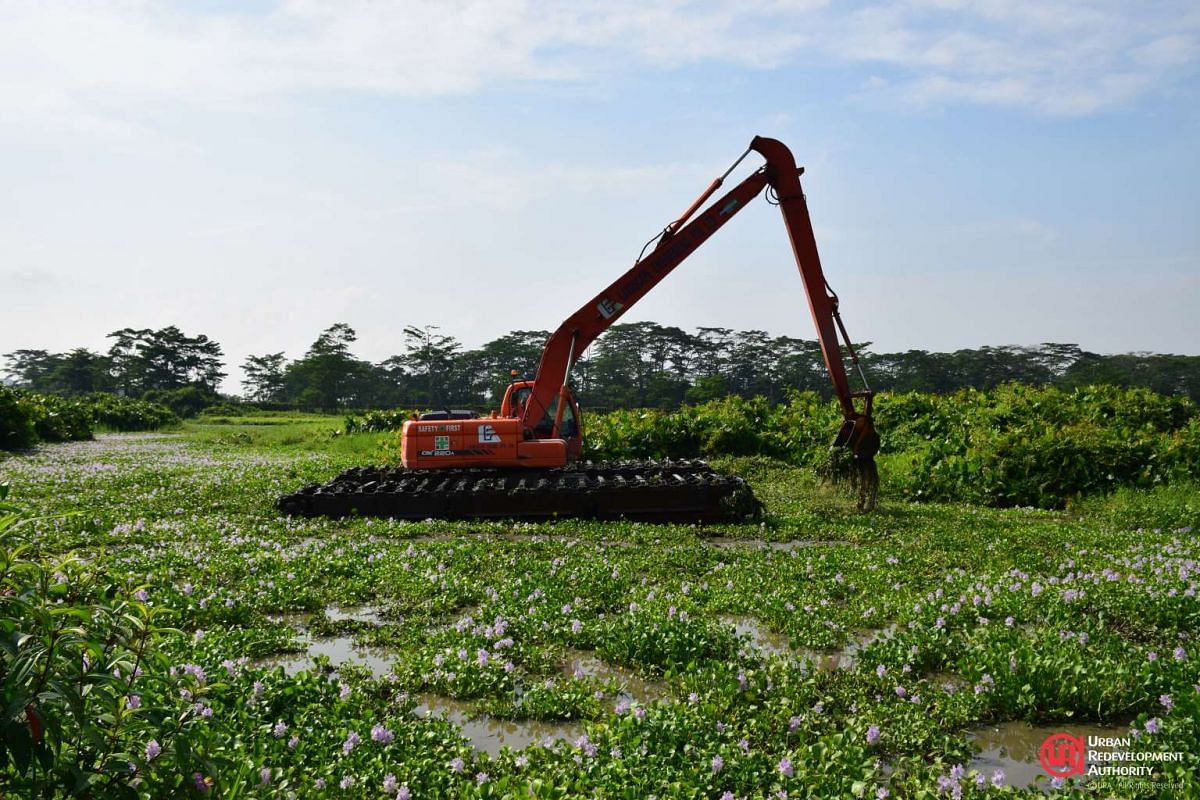 A floating excavator dredging vegetation at Kranji Marshes.