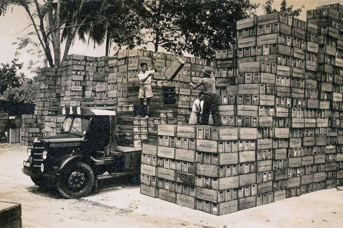 Workers loading wooden crates onto a truck in the 1950s.