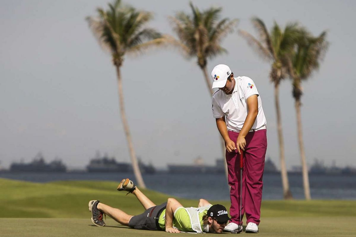 An Byeong Hun of South Korea (right) and his caddy line up a putt on the green of the sixth hole during the third round of the SMBC Singapore Open held at the Serapong Golf course in Sentosa, Singapore on Jan 30, 2016.