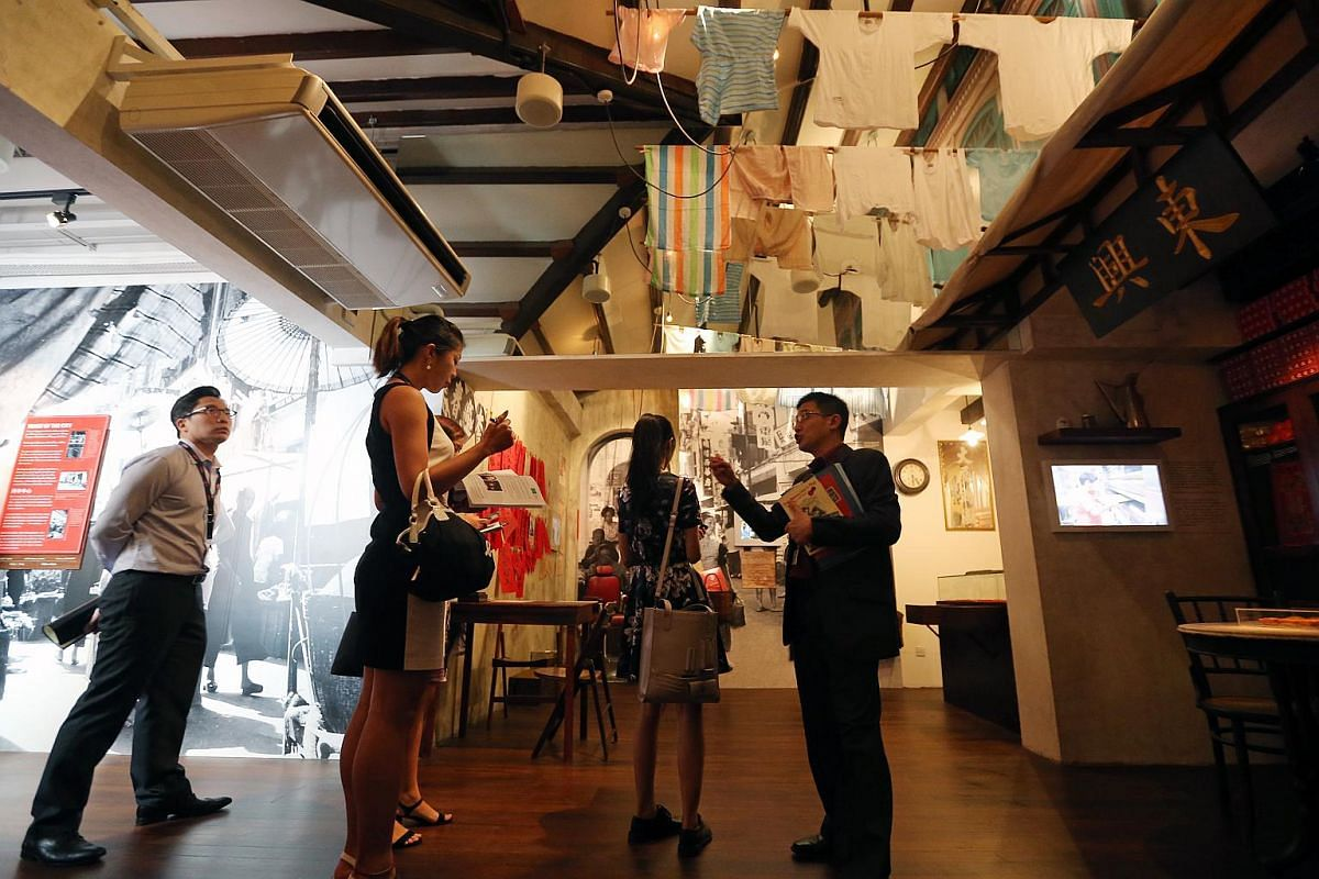 Mr Razeen Chan (right), director for Research, Training and Consultancy at Singapore History Consultants, showing members of the media the gallery illustrating Chinatown in the 1960s.