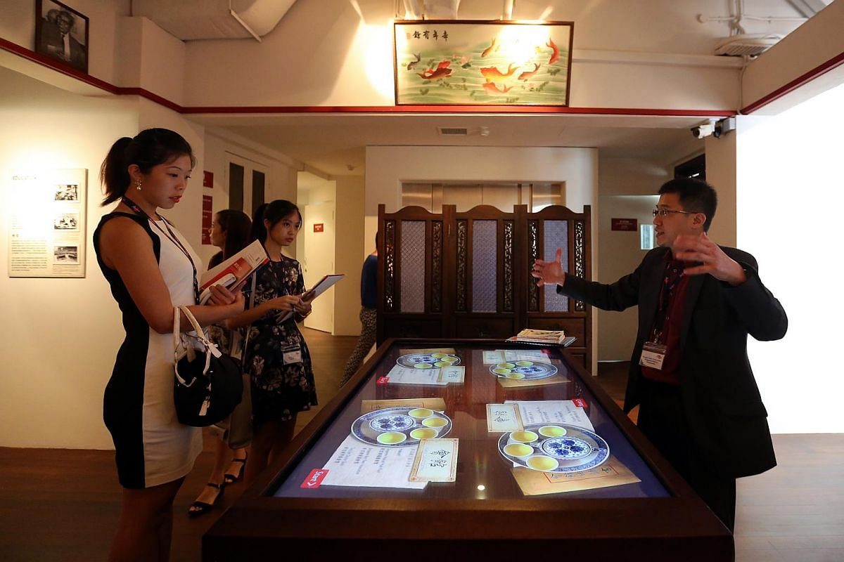 Mr Razeen Chan (right), manager for Research and Consultancy, Singapore History Consultants, shows the media the interactive touchscreen table that allows visitors to trace their Chinese surnames back to their roots.