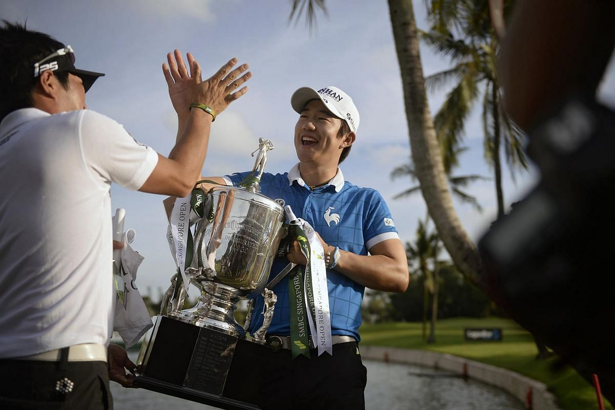 Song Young Han of South Korea (right) high-fives his caddie after winning the SMBC Singapore Open on Feb 1, 2016.