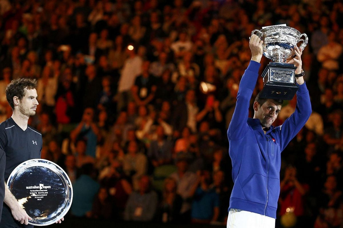 Serbia's Novak Djokovic (right) holding up the men's singles trophy after beating Britain's Andy Murray (left) to win the final match at the Australian Open tennis tournament on Jan 31, 2016.