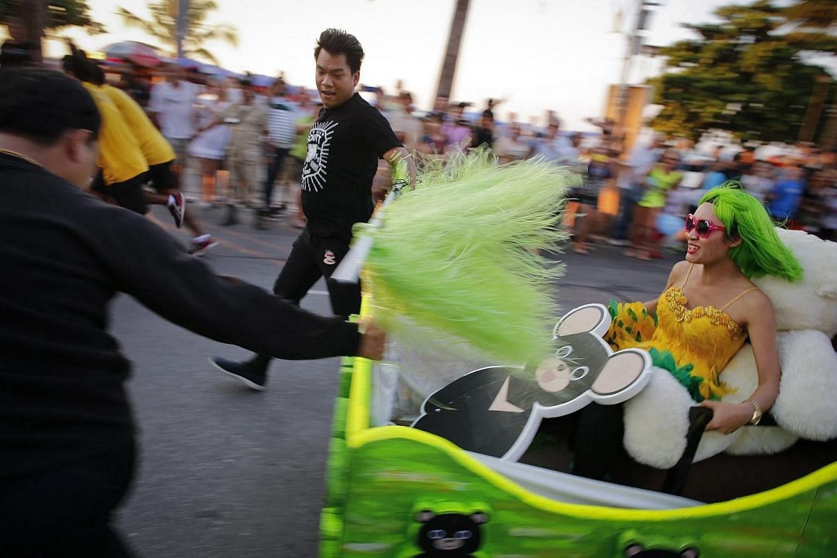 Participants running with their customised beds during the Pattaya Bed Race 2016, in Pattaya, Thailand, on Jan 31, 2016.