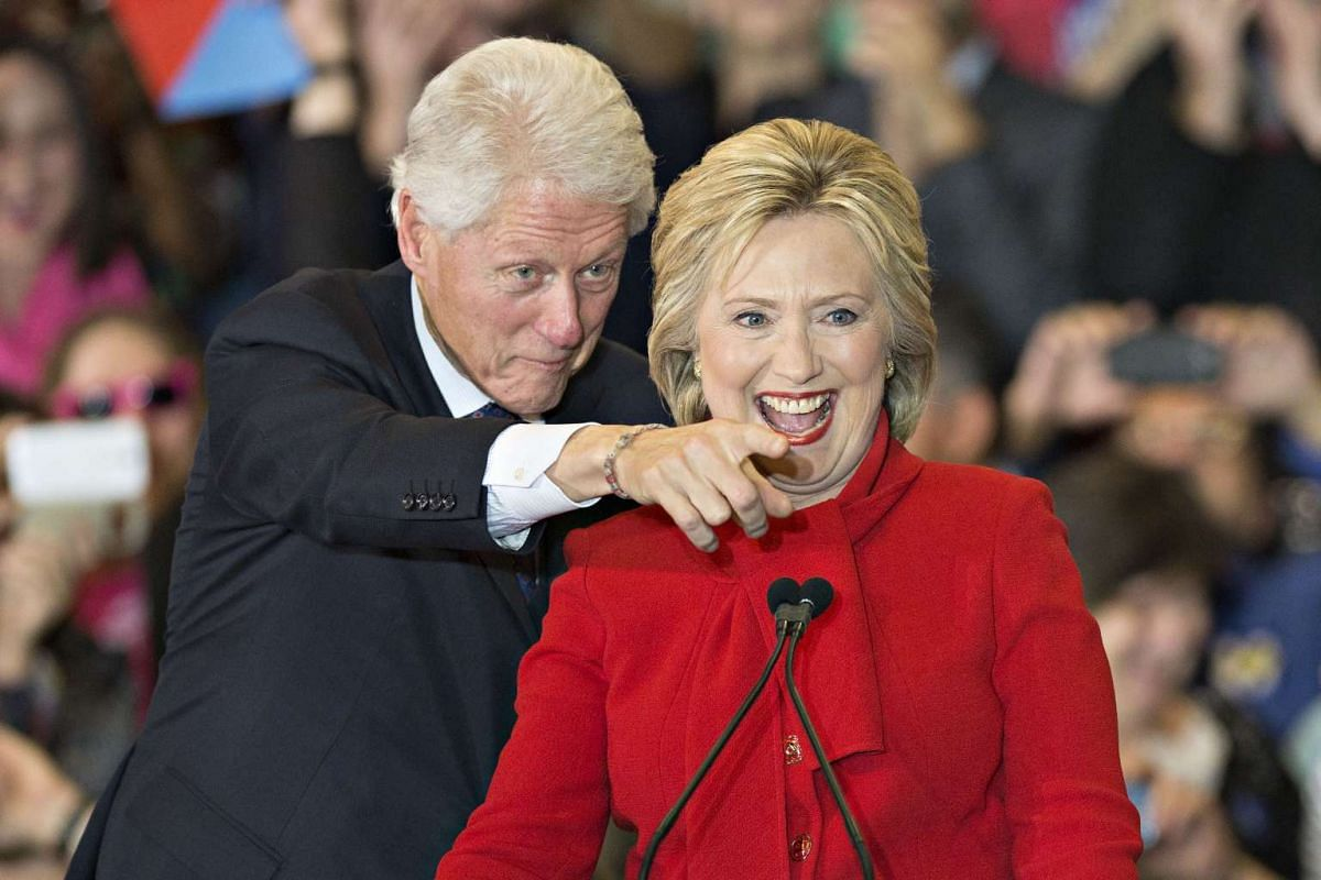 Former US President Bill Clinton pointing out a member of the crowd to his wife and Democratic presidential candidate Hillary Clinton during a caucus night party in Iowa on Feb 1, 2016. Mrs Clinton eked out the narrowest of wins over Senator Bernie S