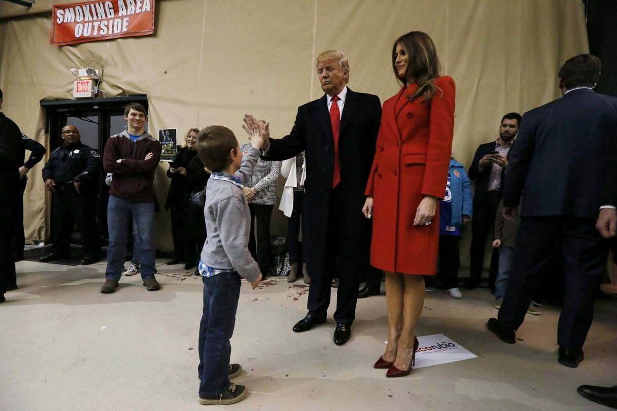 A young boy gives Republican presidential candidate Donald Trump a high-five at the Seven Flags Event Centre in Iowa on Feb 1, 2016.