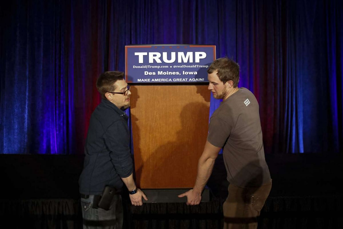 Workers removing the podium of US Republican presidential candidate Donald Trump after his speech following the caucus results in Iowa on Feb 1, 2016.
