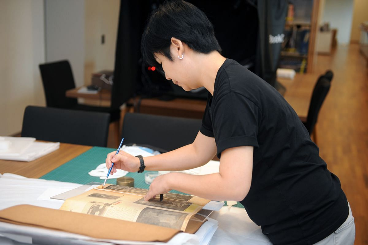 Paper conversation consultant Josephine Chang working on HR Ocampo's scrapbook at National Gallery Singapore.