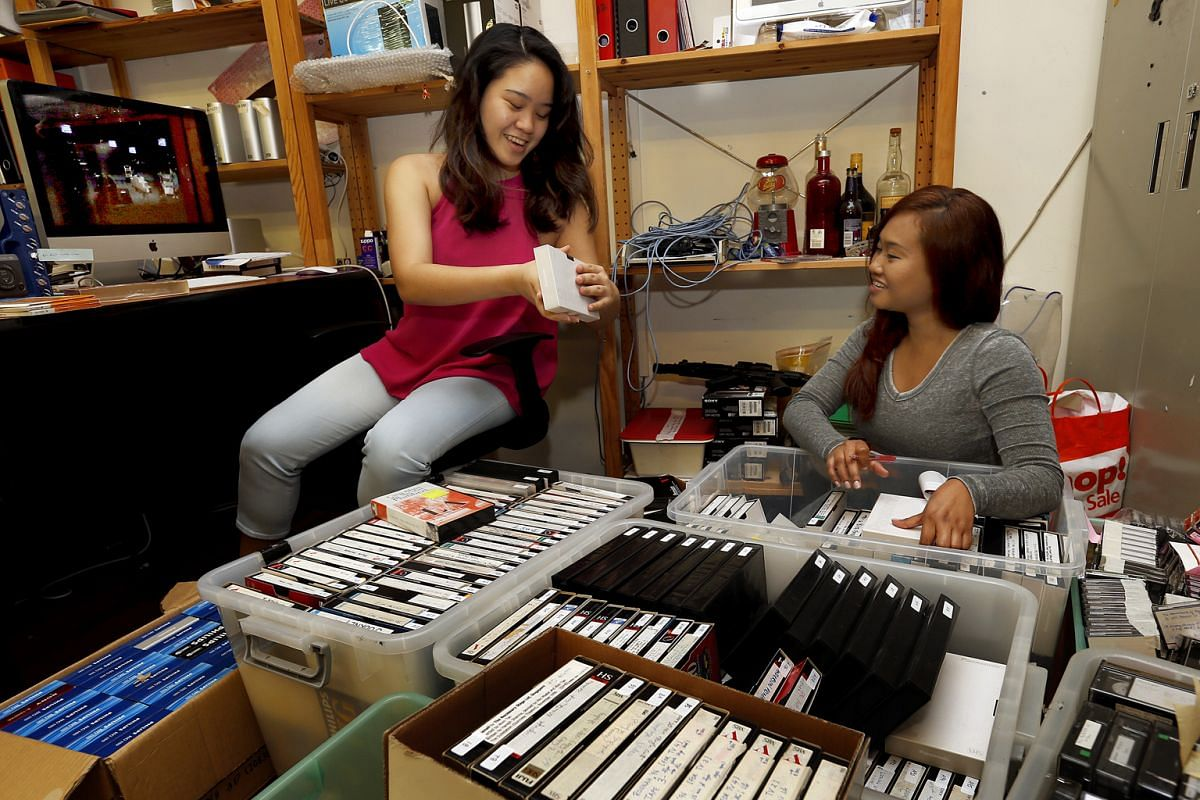 The Necessary Stage's project managers Edlyn Ng (left), 25, and Irma Suzanna Ruslan, 31, with boxes of material for digitisation.
