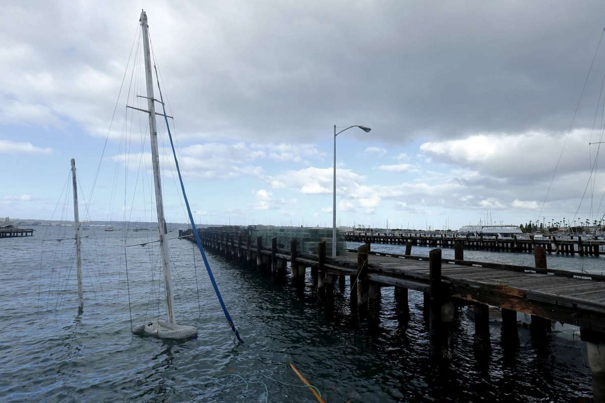 A sunk sailboat sitting next to a pier after a winter storm caused damage to a number of sailboats in San Diego, California, on Feb 1.