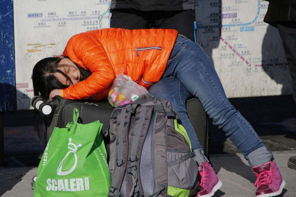 A woman sleeps on her luggage in front of the Beijing Railway Station.