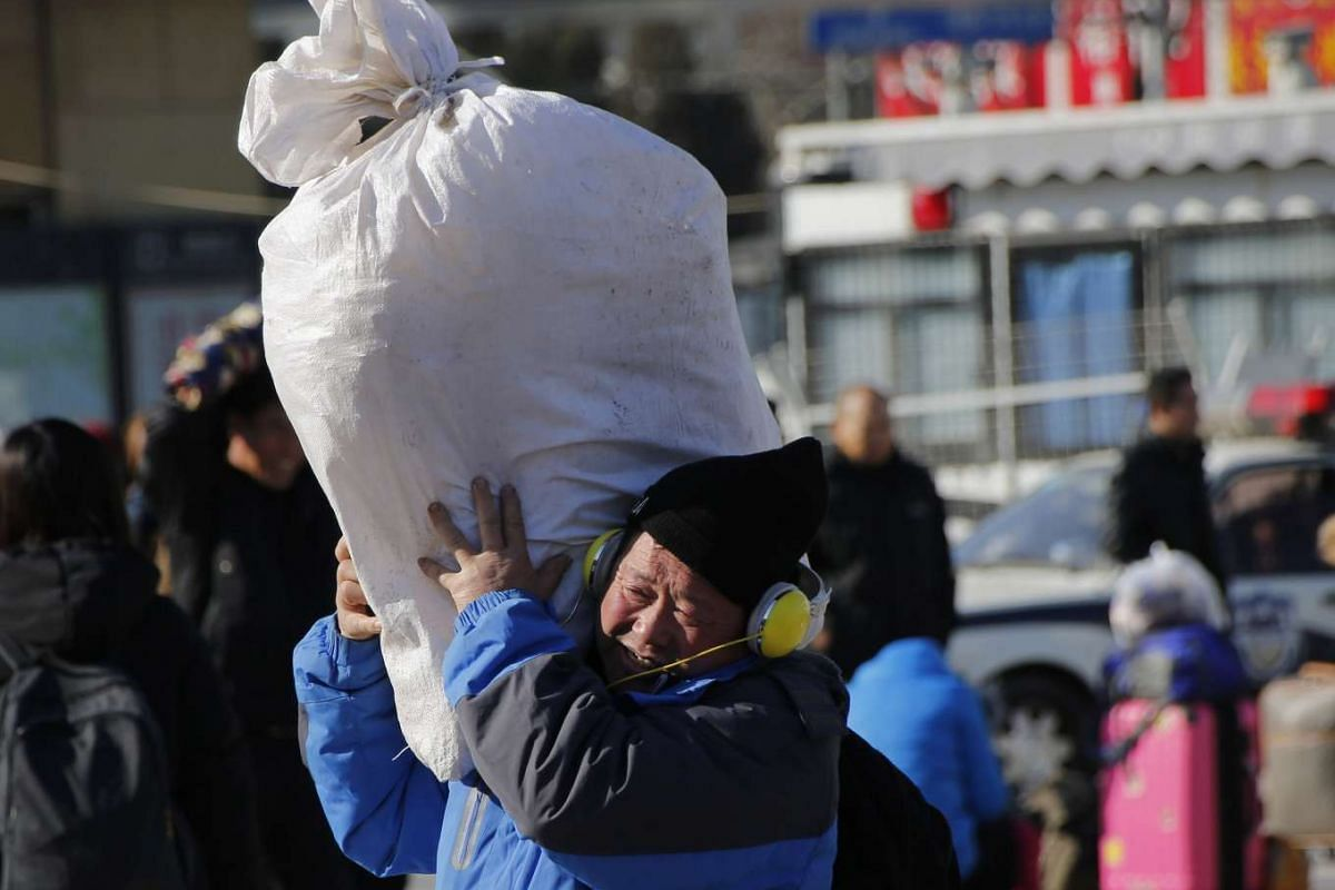 A man carries his sack as he walks towards the Beijing Railway Station.