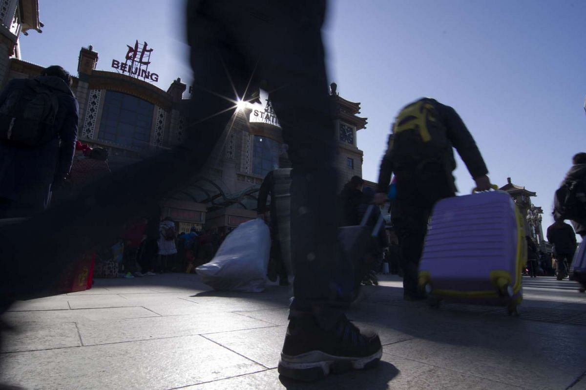 Passengers walk with their luggage at a railway station in Beijing.