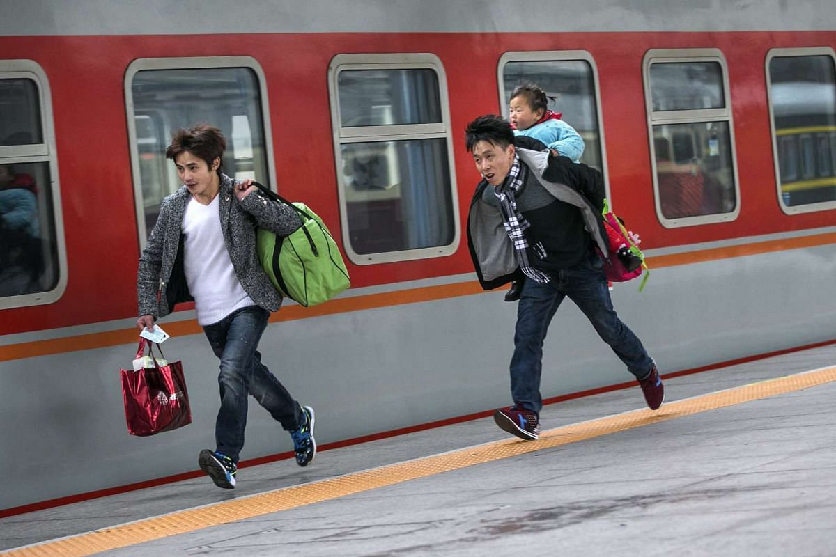Passengers run to catch a train at a railway station in Hangzhou.