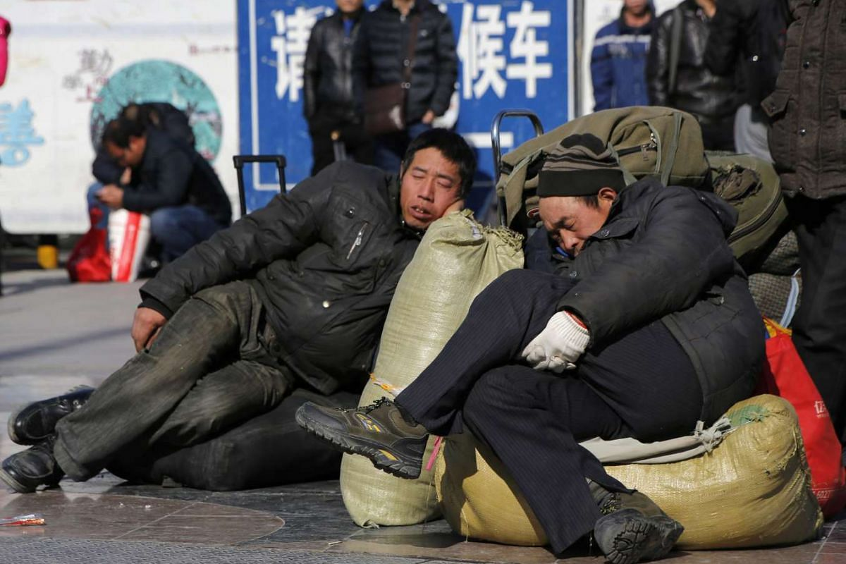 Men sleep on their luggage in front of the Beijing Railway Station while waiting for their trains to arrive.