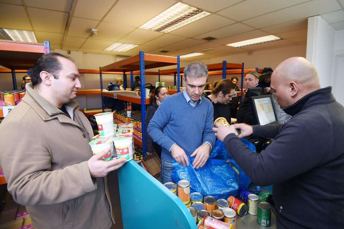 Customers checking out their food items at the new easyFoodstore budget supermarket in Park Royal, north London, Britain on Feb 3, 2016.