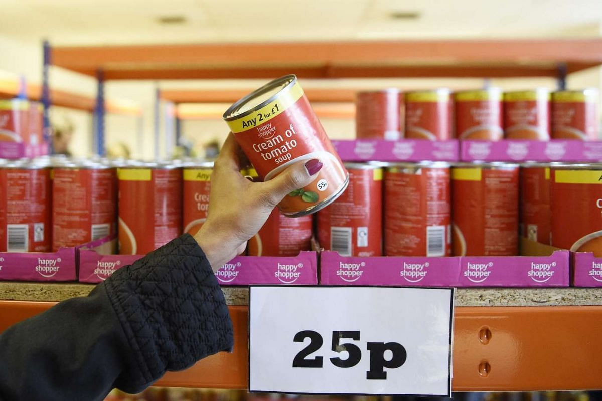 A customer picks a tin of Tomato Soup from a shelf at the new easyFoodstore budget supermarket in Park Royal, north London, Britain on Feb 3, 2016. Every item in the discount store is priced at 25 pence (51 Singapore cents).