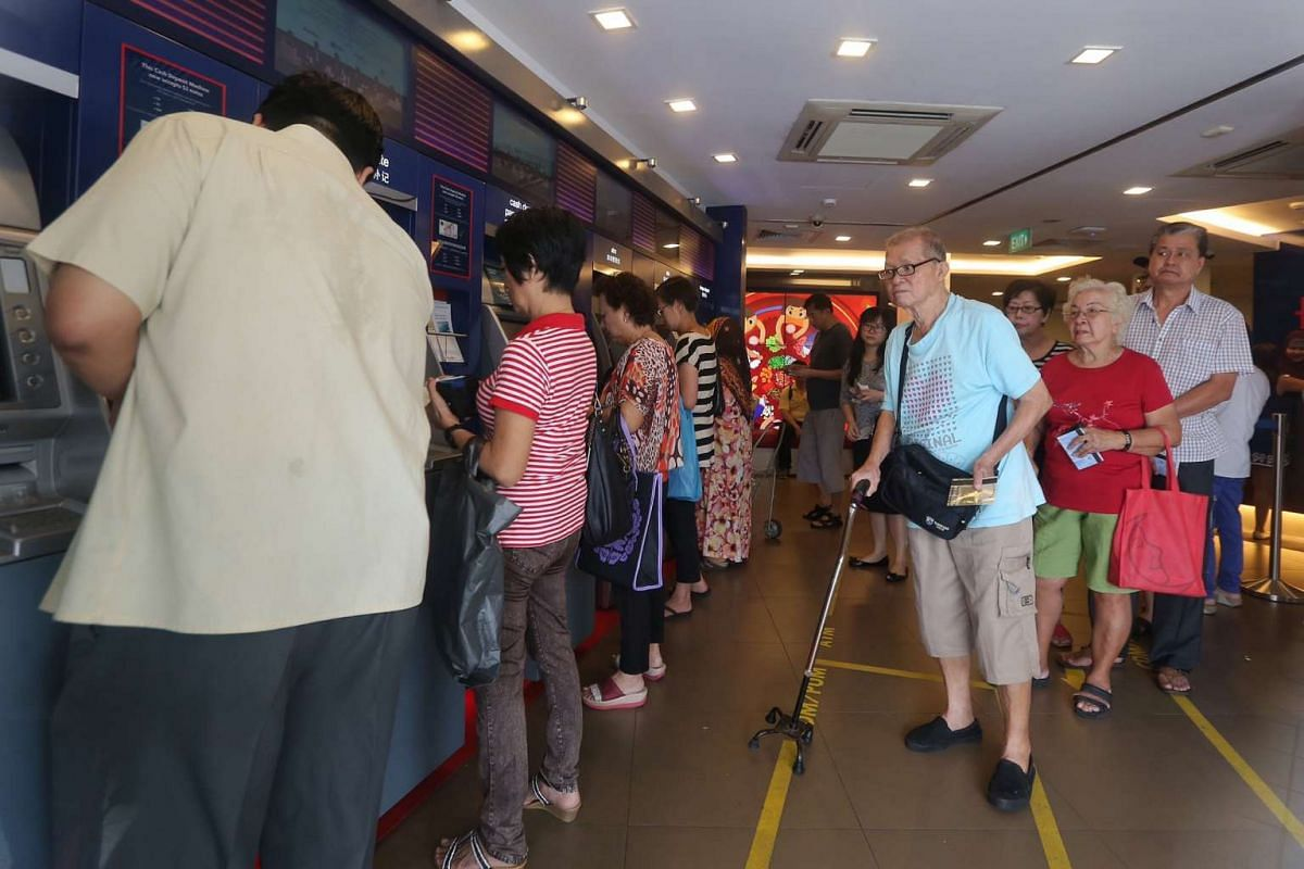 Members of the public queueing to deposit cash at banks in Bedok Town Centre.