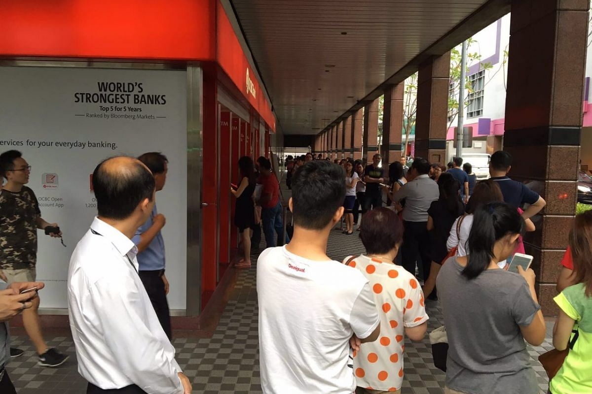 Members of the public queue to deposit money at an OCBC branch in Tampines on Feb 4, 2016.