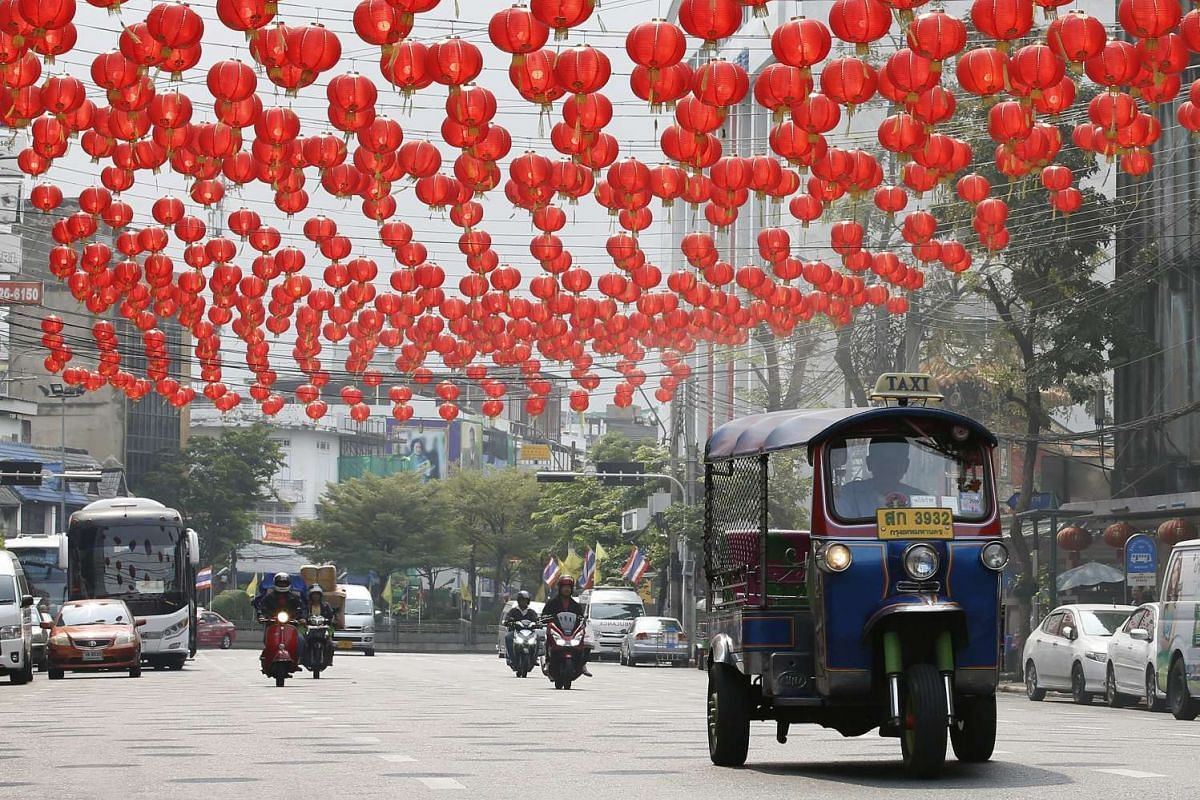 A three-wheeled taxi known as a tuk tuk drives under Lunar New Year banners in Bangkok's Chinatown in Thailand, on Feb 2, 2016.